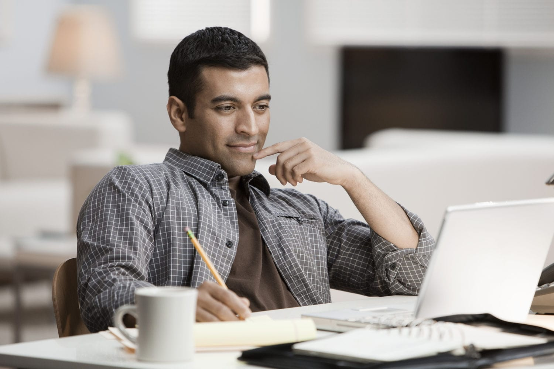 Hispanic man using laptop in home office